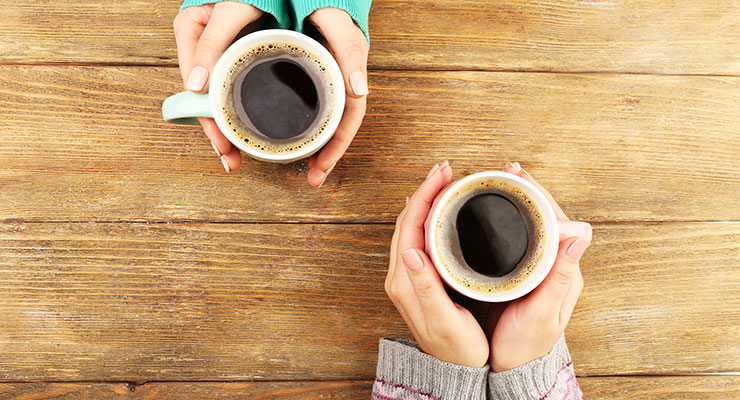 Image of two women's hands holding coffee cups
